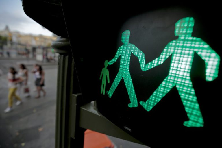 Un semáforo con dos hombres de la mano